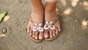 Tanned legs of a little girl in slates with a decorative butterfly. Girl barefoot in summer shoes on sand. Philippines. Tanned legs of a little girl in slates Stock Photos