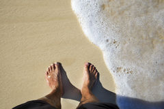 Tanned legs on sand beach Royalty Free Stock Photography