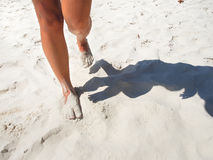 Tanned legs walking on white sand beach Stock Photos