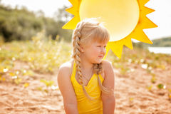 Tanned little blonde posing on sun background Royalty Free Stock Photos