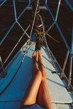 Tanned long legs. Female tanned long legs on the deck of yacht in blue sea Stock Photography