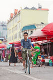 Tanned man cycles on a local outside market, Ruili, China Royalty Free Stock Image