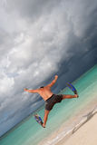 Tanned man jump in blue flippers Stock Photography