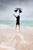 Tanned man jump with umbrella in blue sea Royalty Free Stock Image