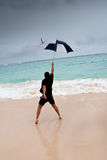 Tanned man jump with umbrella in blue sea Stock Photography