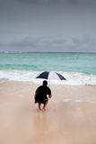 Tanned man jump with umbrella in blue sea Royalty Free Stock Photo