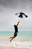 Tanned Man Jump With Umbrella In Blue Sea Royalty Free Stock Images