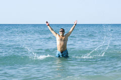Tanned man jumping out of the sea Stock Images