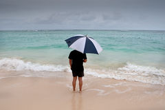 Tanned man stand with umbrella in blue sea Royalty Free Stock Photos