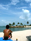 Tanned man sunbathing. Suntanning man on beach, shot from behind him looking towards a tropical seaside scene Stock Photos
