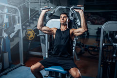 Tanned man training on exercise machine. Active sport workout in gym Royalty Free Stock Photography
