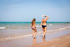 Tanned mother and daughter walking on the beach Royalty Free Stock Photography