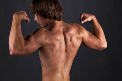 Tanned muscular young man, power bodybuilding. Strong sporty Royalty Free Stock Photography