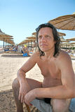 Tanned, an older man sitting on the beach royalty free stock image