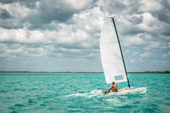 Tanned Sailor. Tanned man sailing his boat in light blue waters Stock Photo