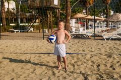 Tanned serious seven-year-old boy in white beach shorts with a ball on a sand volleyball court, vacation royalty free stock photos