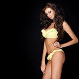 Tanned sexy brunette posing in yellow swimsuit Stock Photo