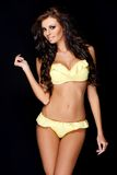 Tanned sexy brunette posing in yellow swimsuit Royalty Free Stock Photo