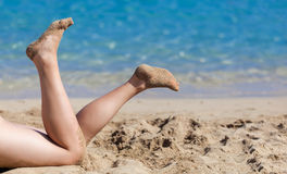 Tanned legs on the beach. Tanned legs of woman on the sandy beach stock images