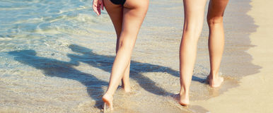 Tanned legs on the beach Royalty Free Stock Photography