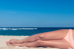 Tanned sexy legs of a woman against the sea, tropical beach scene, Bali island. Stock Image