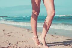 Tanned sexy legs of a woman against the sea, tropical beach scene, Bali island. Stock Photos