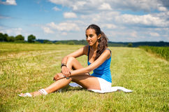 Tanned slender teenage girl in a green field Royalty Free Stock Photos