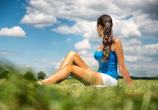 Tanned slender woman sitting in a green field Royalty Free Stock Photography