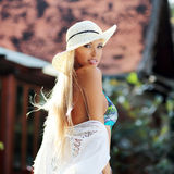 Tanned smiling girl in hat and bikini outdoor Stock Photography