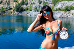 Tanned smiling girl in swimsuit on a mountain lake holding watch Royalty Free Stock Images