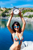 Tanned smiling girl in swimsuit on a mountain lake holding watch Stock Photography
