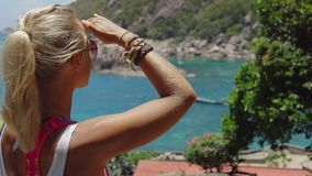 Tanned sporty female admire the gorgeous Tanote Bay on sunny day. Light ocean breeze ocean breeze sifted through her. Blond hair. Koh Tao, Thailand stock video