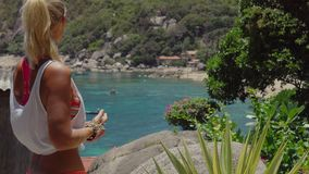 Tanned sporty female enjoy gorgeous view of Tanote Bay on sunny day. Light ocean breeze ocean breeze sifted through her. Blond hair. Koh Tao, Thailand stock footage