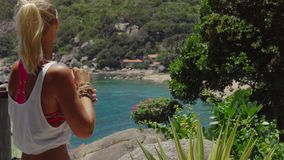Tanned sporty female enjoy gorgeous view of Tanote Bay on sunny day. Light ocean breeze ocean breeze sifted through her. Blond hair. Koh Tao, Thailand stock video