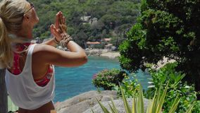 Tanned sporty female meditating in front of gorgeous Tanote Bay on sunny day. Light ocean breeze ocean breeze sifted. Through her blond hair. Koh Tao, Thailand stock footage