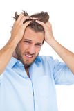 Tanned stressed man holding his hair Stock Photo