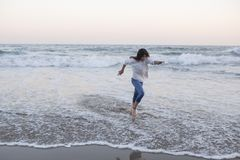 Tanned teen girl running at sunset on the shore of the Mediterranean dressed in white sweatshirt and jeans stock photo