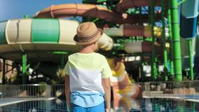 Tanned travel little boy in hat jumping raising hand rejoicing holiday at outdoor aquapark back view