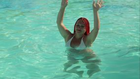 Tanned woman with African pigtails dancing in the pool with raised hands