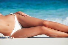 Tanned woman in bikini. Tanned woman body in red bikini laying in beach, blue sea water in background royalty free stock image