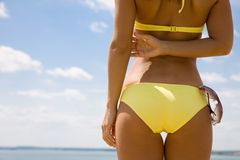 Tanned woman body in bikini. Torso of luxurious woman with sunglasses. Back view Stock Image
