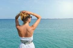 Tanned woman in dress facing seaside. Suumer vacation Stock Images