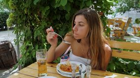 Tanned woman eating on the outdoor summer terrace. 4k stock video