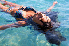Tanned woman floating on sea Royalty Free Stock Images