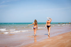 Tanned woman and girl walking on the seashore Royalty Free Stock Photos