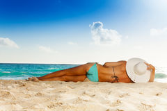 Tanned woman laying on white sand beach Stock Images