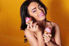 Tanned  woman with long dark curly hair,wears lingerie, holding sweet cakes Stock Image