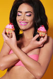 Tanned  woman with long dark curly hair,wears lingerie, holding sweet cakes Stock Photo