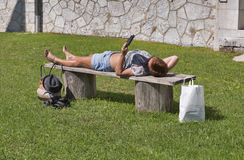 Tanned woman lying on a bench and reading electronic book Royalty Free Stock Images
