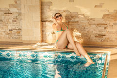 Tanned woman lying at pool on sunny day Royalty Free Stock Photography